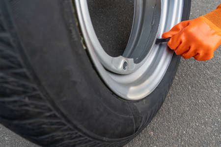 Close-up of a sleeve of orange gloves twists off the nipple cover on a car wheel.