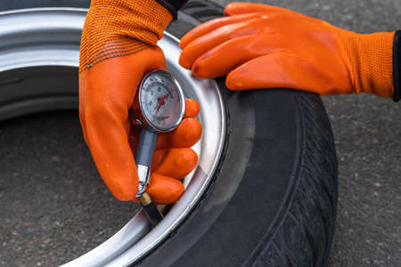 A woman checks the pressure in a car tire with a pressure gauge, close-up. Machine maintenance 스톡 콘텐츠