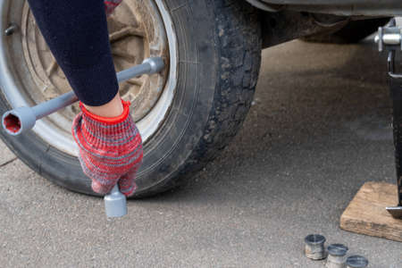 A woman with a wheel wrench unscrews a wheel from a car to replace it. Car repair 스톡 콘텐츠