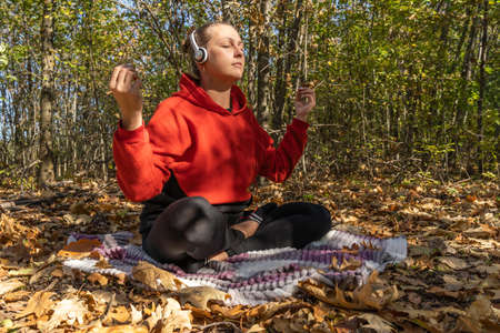 Woman in the autumn forest meditates with headphones sitting on a blanket. Outdoor recreation