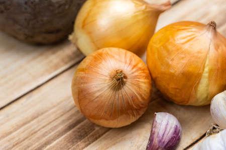 Three onions on a wooden background. Close-up Reklamní fotografie
