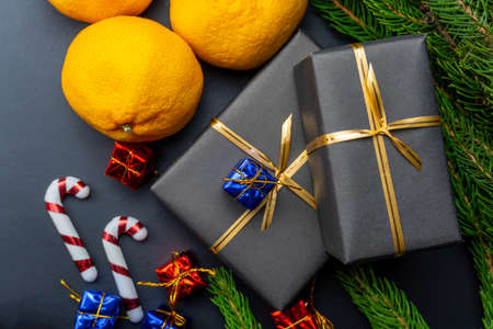 Gifts, tangerines, fir branches on a black background. Christmas background. Close-up.