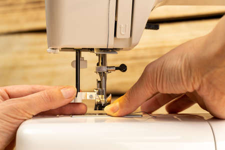Woman's fingers putting thread in needle loop on electric modern sewing machine for start sewing. Steel needle with looper and presser foot. Close up view of female working hands. Blurred background.
