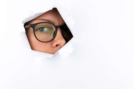A woman's eye with black-framed glasses looks through a hole in a white paper wall. Espionage concept. Free space for text.