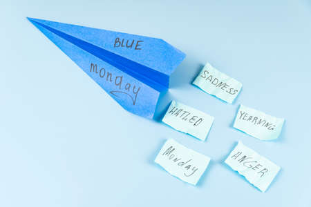 A flying blue paper airplane with the inscription Blue Monday against a blue sky and throwing stickers with the words. Flying bad mood concept