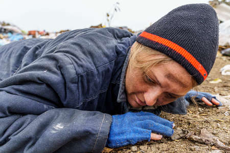A dirty woman in torn clothes lies on the ground in front of a dump. Homeless woman lives in the open air