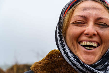 Close-up of a dirty woman's face. A dirty bum smiles and shows black teeth on the background of a landfill. Free space for text