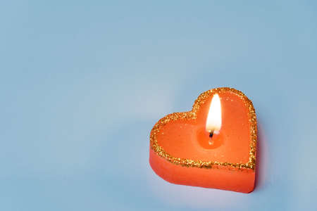 burning candle in the shape of a heart on a blue background - a symbol of love. Valentine's Day. The concept of dating, romance.