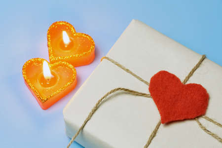A pair of red candles in the shape of a heart on a blue background and next to a gift for Valentine's Day. Gift concept to loved one