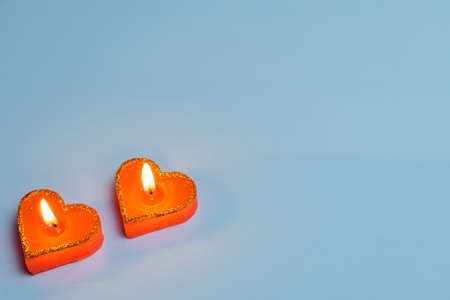 Two red burning candles in the shape of a heart on a blue background - a symbol of love. Valentine's Day. The concept of dating, romance.