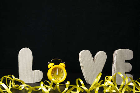 Surround white letters LOVE, yellow alarm clock instead of the letter O and yellow serpentine on the background. Free space for text. Valentine's day card.