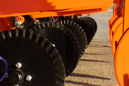Red and black wavy discs for agricultural drills. Land cultivation concept