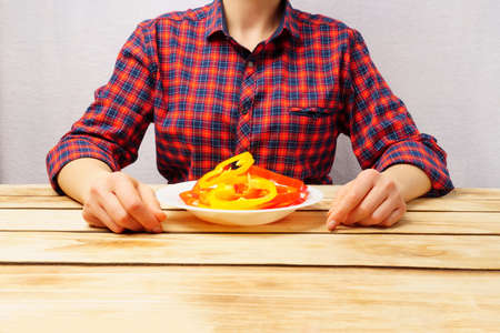 Fresh slices of sweet peppers on a white plate in the background a woman in a red plaid shirt. Proper nutrition