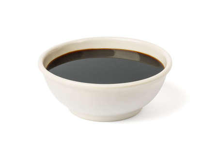 soy sauce in a bowl on a white background. in a white plate or bowl, dark brown sauce Zdjęcie Seryjne