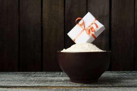 gift box fell into flour, dark wood background, free space for text