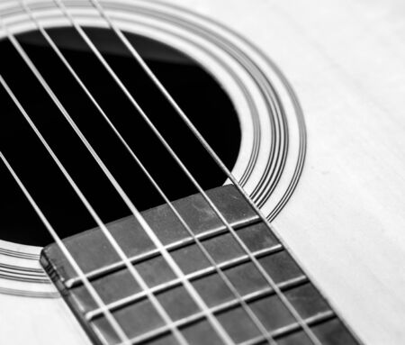 brown background: Guitar Strings, close up. Acoustic guitar. Black and white.