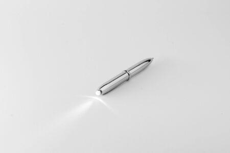 torch light: Modern silver pen with torch light. Stock Photo