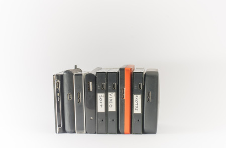 digital data: Bunch of external hard drives. Isolated on white. Close up.
