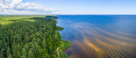 Aerial shot along the coast. Forest. Lake. Panorama. Stock Photo