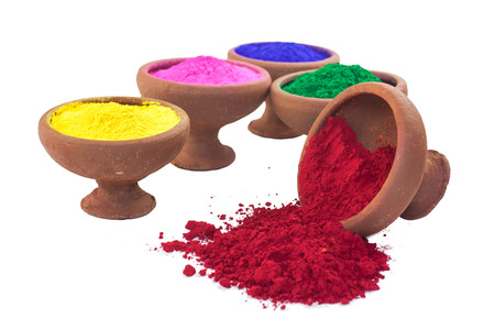 A variety of colored dyes in earthen bowls isolated on white  The red color is spilled   Stock Photo