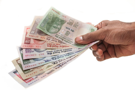 An Indian hand holding a fan of Indian rupees isolated on a white background  Banque d'images