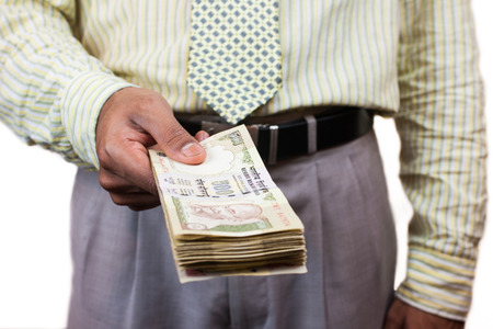 rupee: An Indian business man holding out a stack of 500 rupee notes