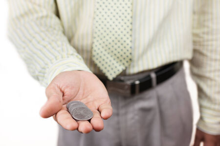 A business man holding a handful of loose change