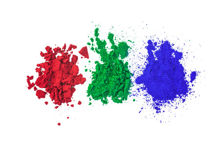 splattered: Red Green and Blue Dye Powders splattered on a White Background.