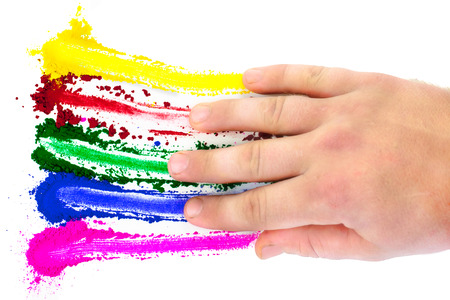 smeared: A spectrum of colors being smeared across a white background by a hand. Stock Photo