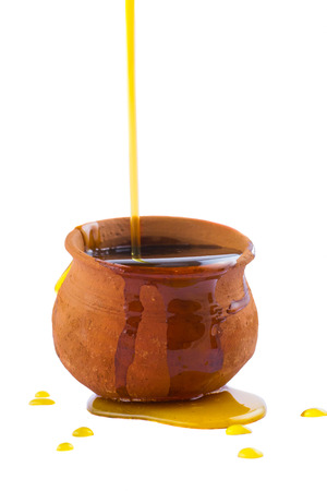 Honey pouring into an overflowing clay pot. Isolated on a white background.