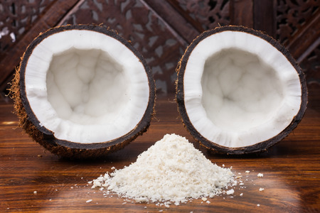 shredded coconut: Coconut halves with shredded coconut in the foreground. Stock Photo