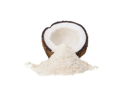 A Coconut Half and a Pile of Shredded Coconut Isolated on a White Background.