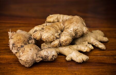 ginger root: Fresh ginger root on a dark wooden surface.