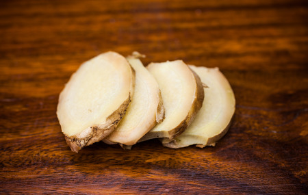 ginger root: Ginger root slices laying on a dark wood surface.