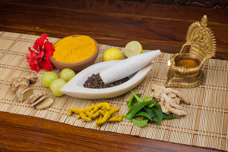 A selection of natural ingredients arranged in and around a marble mortar and pestle.