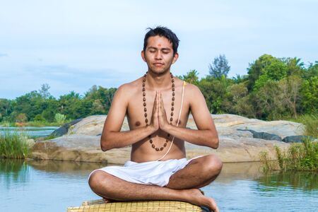 legs folded: A young brahmin in meditation with folded hands on a river bank.