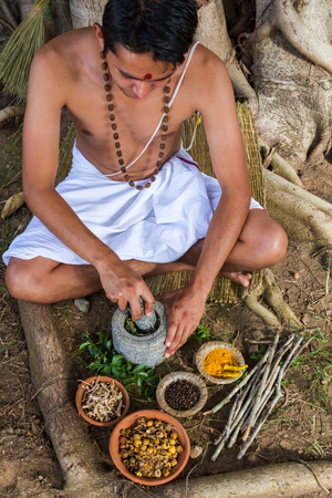 A young man preparing ayurvedic medicine in the traditional manner. Фото со стока