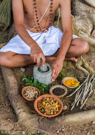 A young man preparing ayurvedic medicine in the traditional manner. Standard-Bild