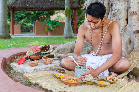 A young man preparing ayurvedic medicine in the traditional manner. Stock Photo