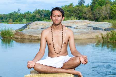 dhyana: A young brahmin sits in meditation on a river bank. Stock Photo