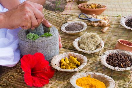 manos asiático que se prepara la medicina ayurvédica con mortero de granito y mortero.