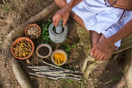 Un giovane uomo la preparazione di medicina ayurvedica in modo tradizionale.