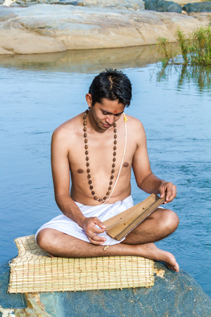 vedas: A young brahmin reads an ancient Hindu scripture on a river bank. Stock Photo