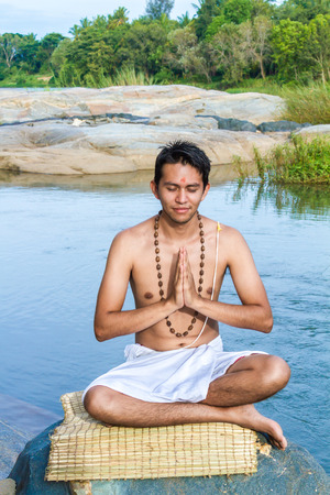 dhyana: A young brahmin in meditation with folded hands on a river bank.