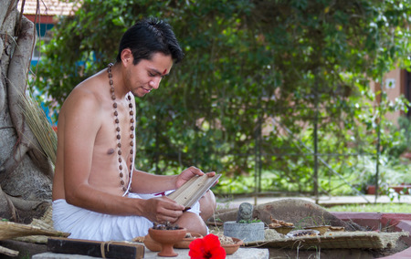 vedas: A young brahmin reads an ancient Hindu text surrounded by natural medicinal ingredients. Stock Photo