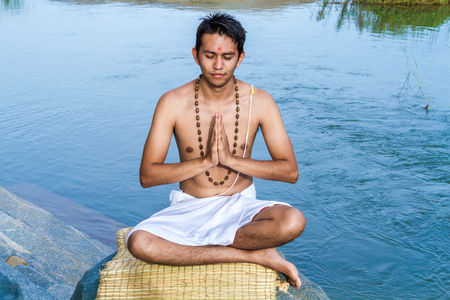 cross legs: A young brahmin with folded hands on a river bank.
