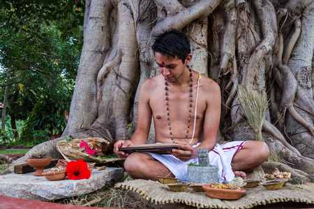 A young brahmin reads an ancient Hindu text surrounded by natural medicinal ingredients. Stock Photo
