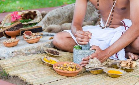Un giovane uomo la preparazione di medicina ayurvedica in modo tradizionale. Archivio Fotografico