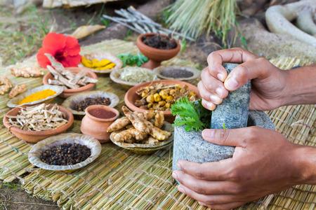 Asian hands preparing ayurvedic medicine with granite mortar and pestle.