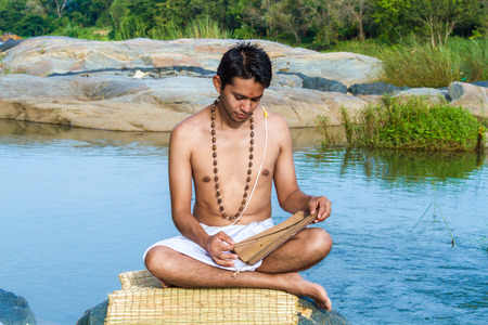 A young brahmin reads and ancient Hindu scripture on a river bank.